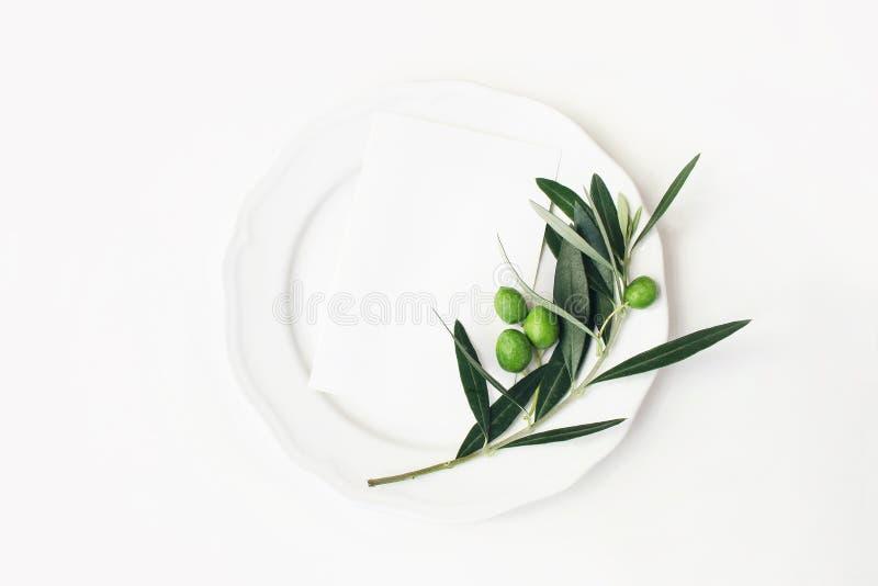 Ajuste festivo del verano de la tabla con las hojas, la rama y la fruta verdes olivas en la placa de la porcelana Escena en blanc foto de archivo libre de regalías