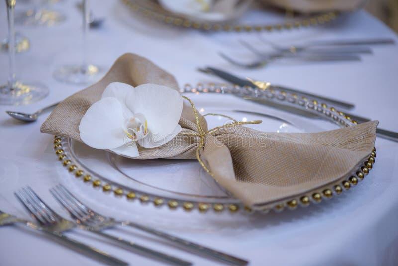 Ajuste fino de la mesa de comedor que ofrece las placas transparentes, la servilleta de lino beige con la orquídea natural y deco fotografía de archivo
