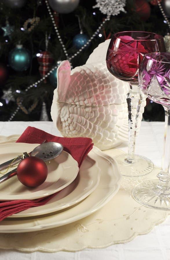 Ajuste hermoso de la tabla de la Navidad delante del árbol de navidad, con los vidrios cristalinos rojos del cubilete del vino -  fotos de archivo libres de regalías