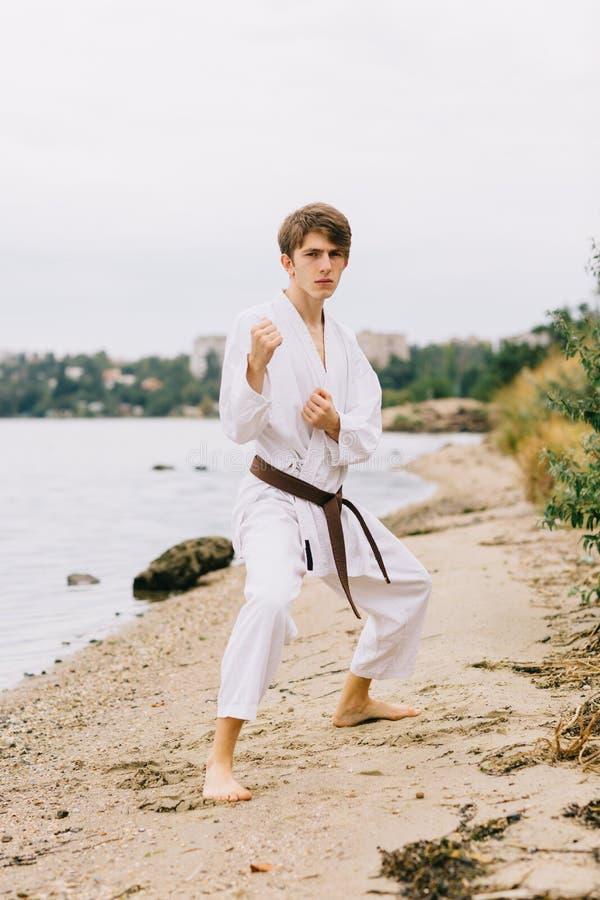 Ajuste, judô praticando do homem forte, novo em um fundo natural Conceito tradicional do uniforme do karaté foto de stock