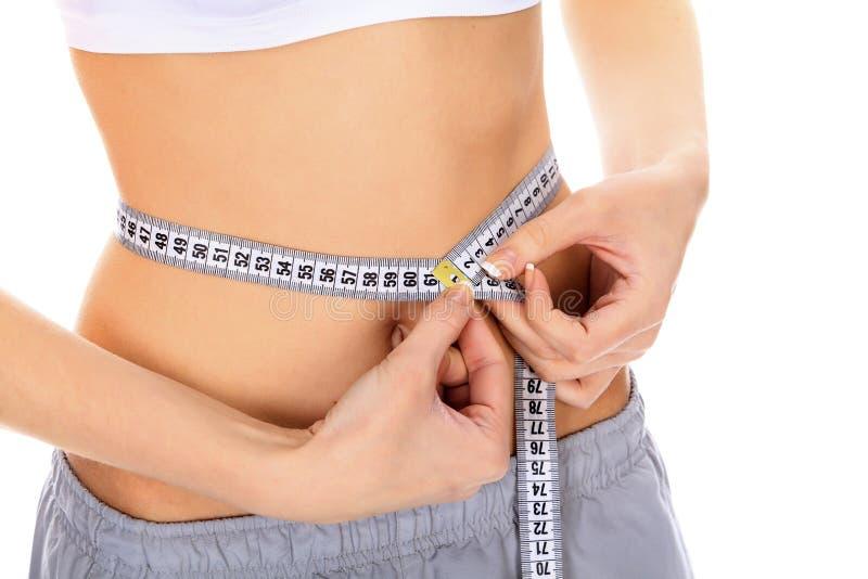 Ajuste a la mujer joven que mide su cintura imágenes de archivo libres de regalías