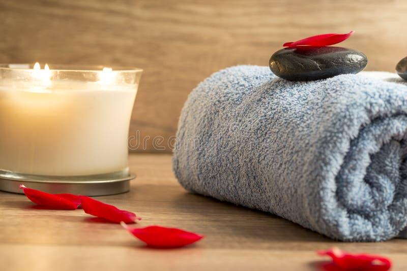 Ajuste lujoso con una toalla azul rodada, vela romántica del balneario foto de archivo libre de regalías