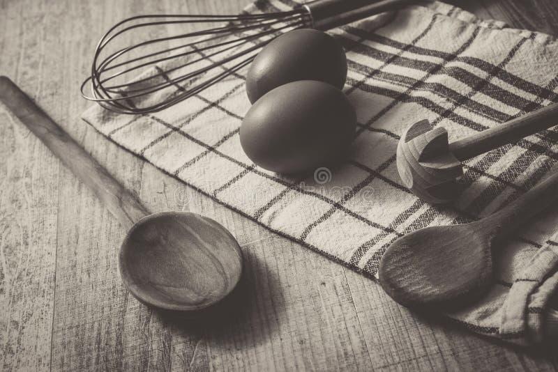 Ajuste monocromático da cozinha com 2 ovos, toalha, colher de madeira e Querl e um Eggbeater em uma tabela fotos de stock royalty free