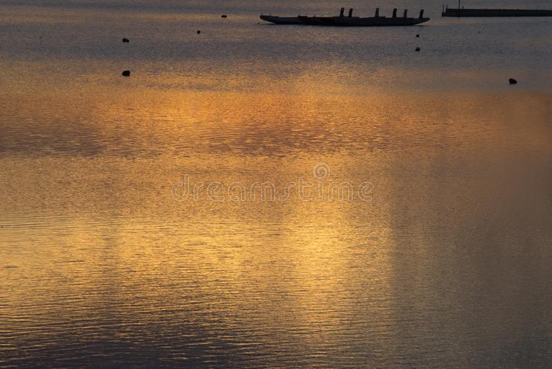 Ajuste morno do sol na água calma imagem de stock royalty free