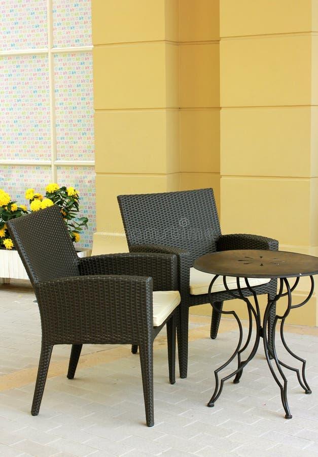 Ajuste de la tabla y de la silla con la flor en restaurante al aire libre foto de archivo