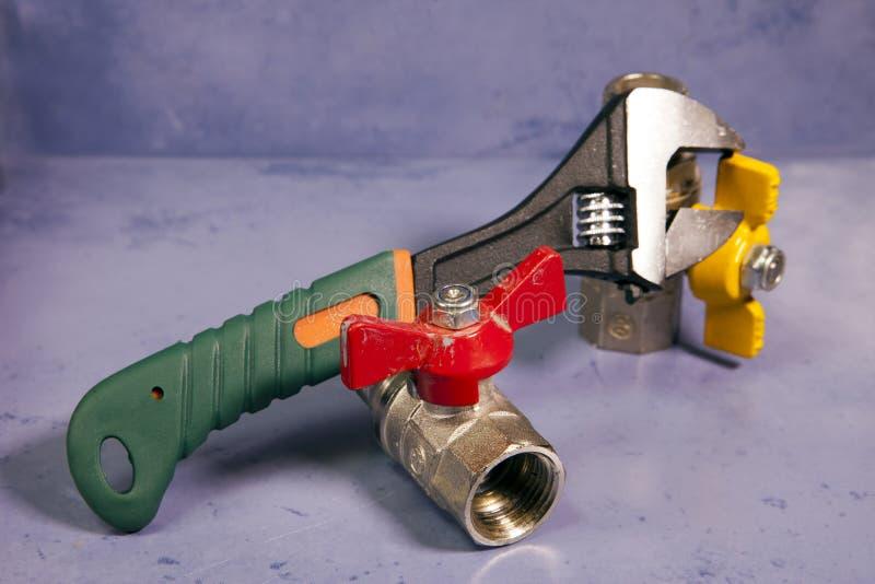 Ajuste o aperto do poder da chave e os elementos das válvulas de desligamento da água e do gás, profundidade pequena da agudeza fotografia de stock