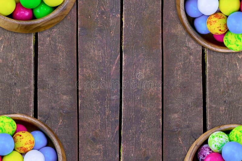 ajuste quatro bacias de branco azul azul do amarelo doce redondo brilhante colorido dos doces em um fundo vertical da placa fotografia de stock