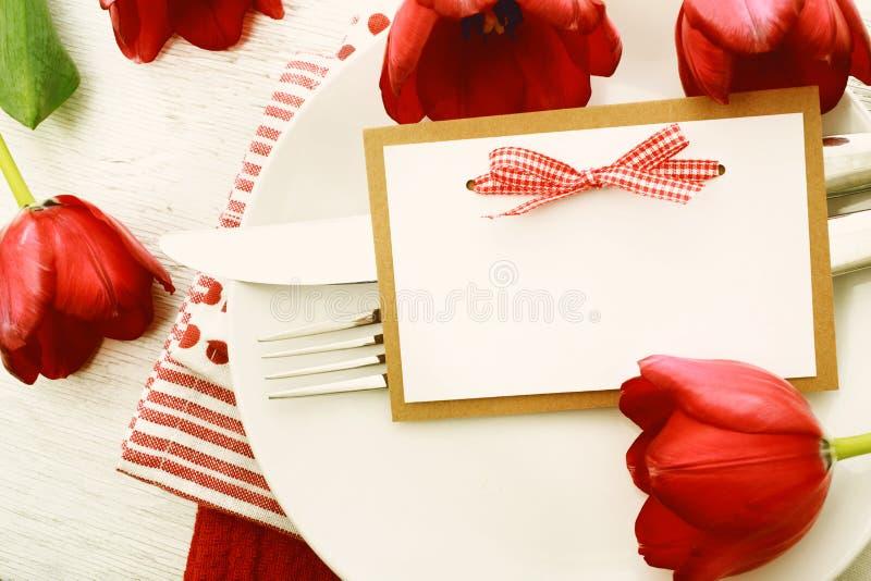 Ajuste romântico da tabela de jantar com o cartão de nota vazio fotos de stock royalty free