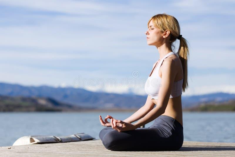 Ajuste y mujer joven deportiva que hacen yoga al lado del lago imagenes de archivo