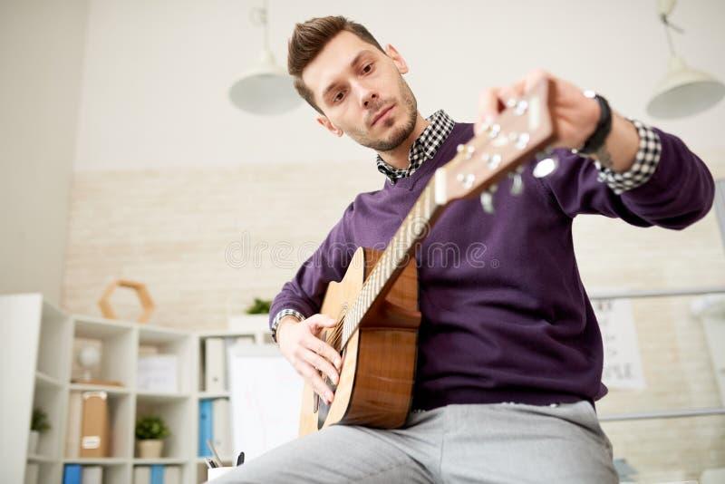 Ajustement de la guitare au bureau moderne photo stock