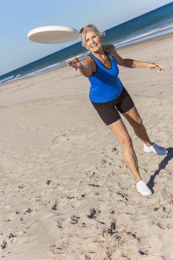 Femme supérieure en bonne santé jouant le frisbee à la plage images libres de droits