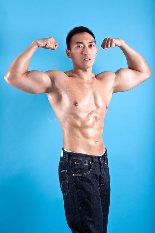 ajustement et homme asiatique musculaire en denim noir photographie stock libre de droits