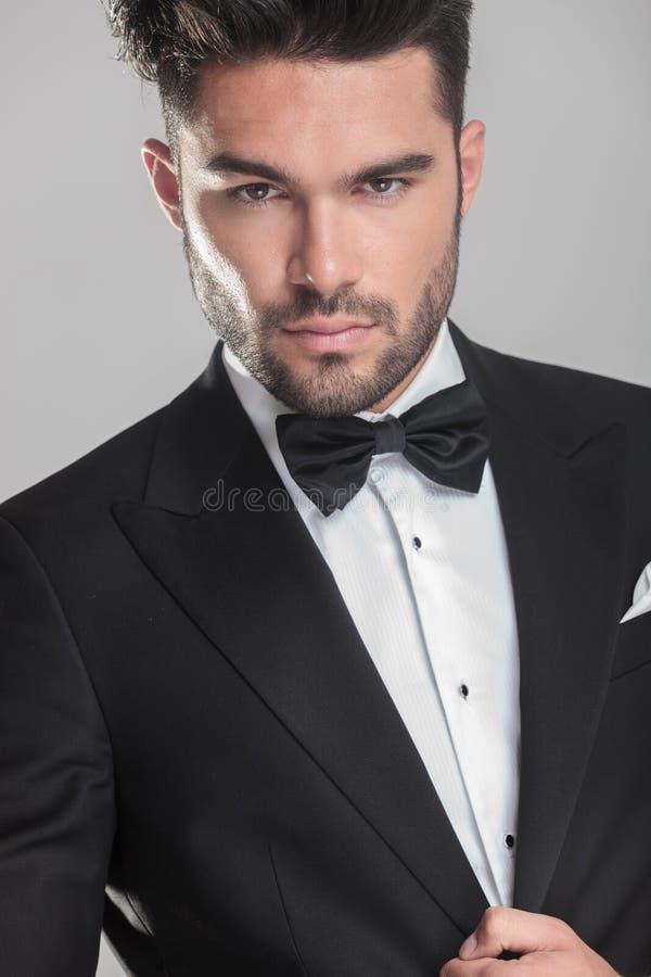 ajusting他的夹克的无尾礼服的英俊的年轻人 库存照片