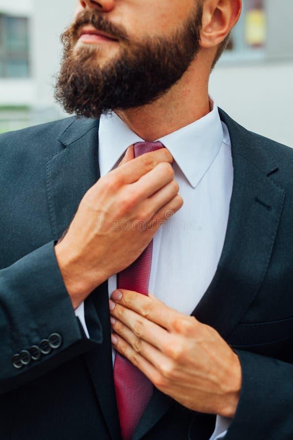 ajusting他的年轻可爱的商人领带 室外照片 免版税库存图片