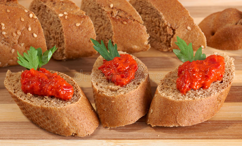 Ajvar on bread slices. Red pepper ajvar puree on bread slices royalty free stock photos