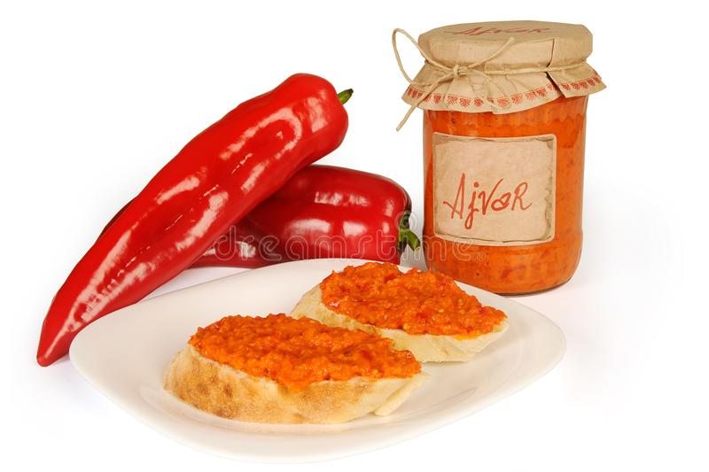 Ajvar - delicious dish of red and green peppers, onions, garlic, eggplant. Ajvar in jar. Sauce spread on two slices of bread on pl royalty free stock photo