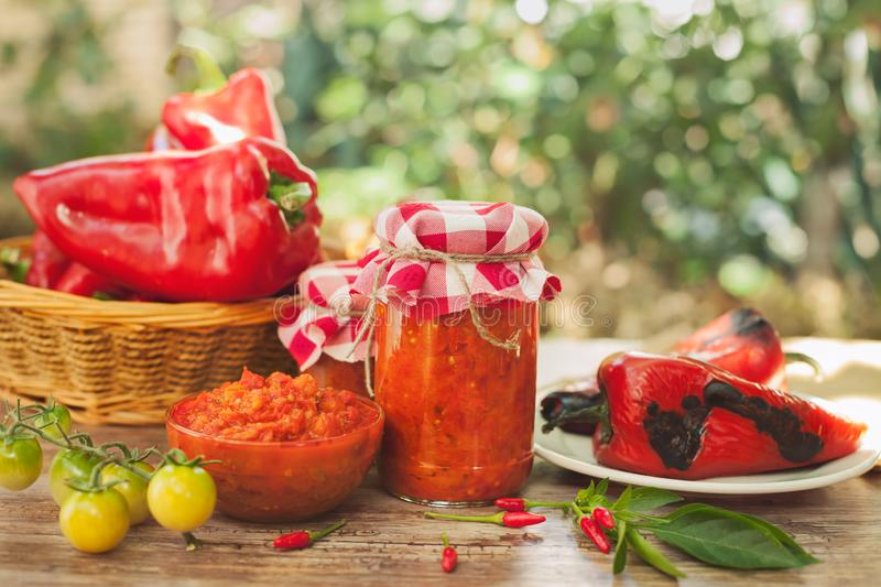 Ajvar in a glass jar and glass bowl. On the table stock photography