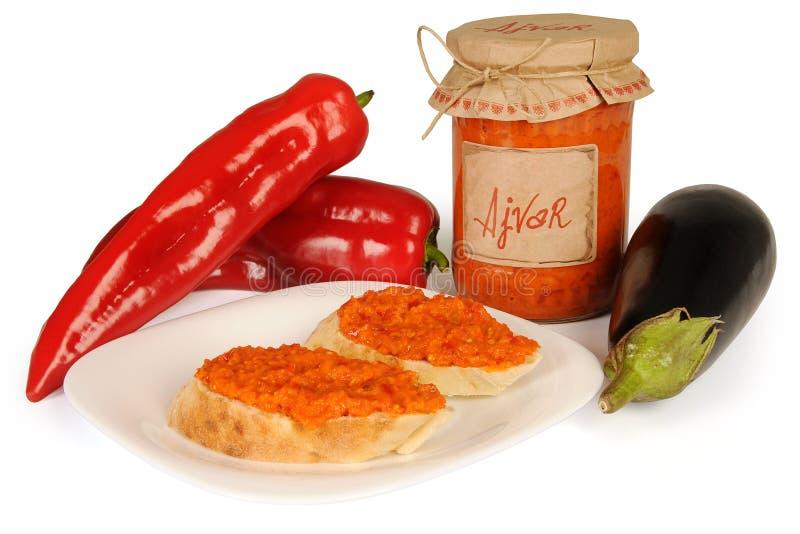 Ajvar - piatto delizioso di rosso e di peperoni verdi, cipolle, aglio, melanzana Ajvar in barattolo La salsa si è sparsa su due f fotografia stock