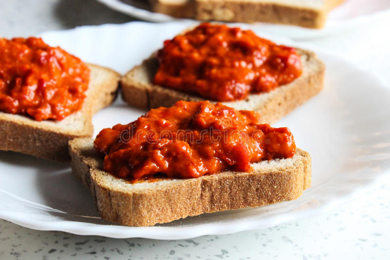 Ajvar. Serbian salad ajvar and toasted bread on a plate stock images