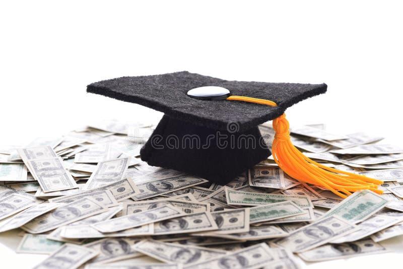 Akademikermössa på en hög av pengar som föreställer den höga kostnaden av utbildning, studenten Loans och bestickning royaltyfri fotografi