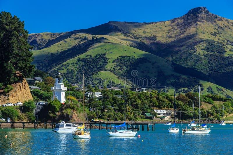 Akaroa, Nuova Zelanda Una vista attraverso l'acqua al faro storico immagine stock
