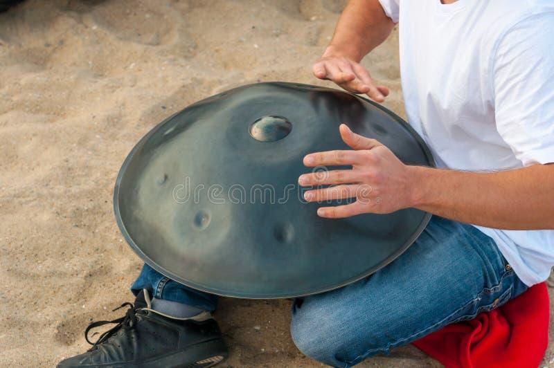 akci zamkniętego dobosza instrumentu muzykalny fotografii sztuka proces muzykalny faceta obsiadanie na plaży i bawić się handpan  zdjęcie stock