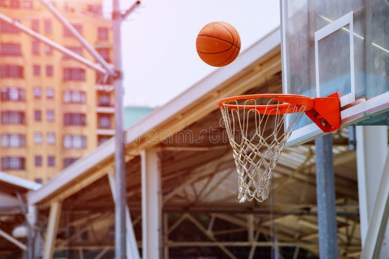 Akcja strzał koszykówka spada koszykówki sieć na parkowym tle i obręcz zdjęcia stock