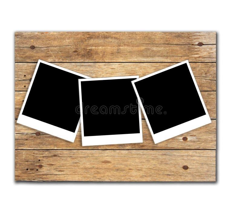 Akcyjna fotografia: Polaroid fotografii ramy na starym drewnianym tle zdjęcia royalty free