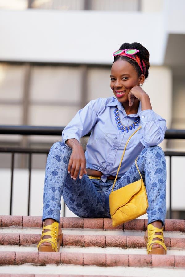 Akcyjny wizerunek kobiety obsiadanie na schodkach i ono uśmiecha się fotografia royalty free