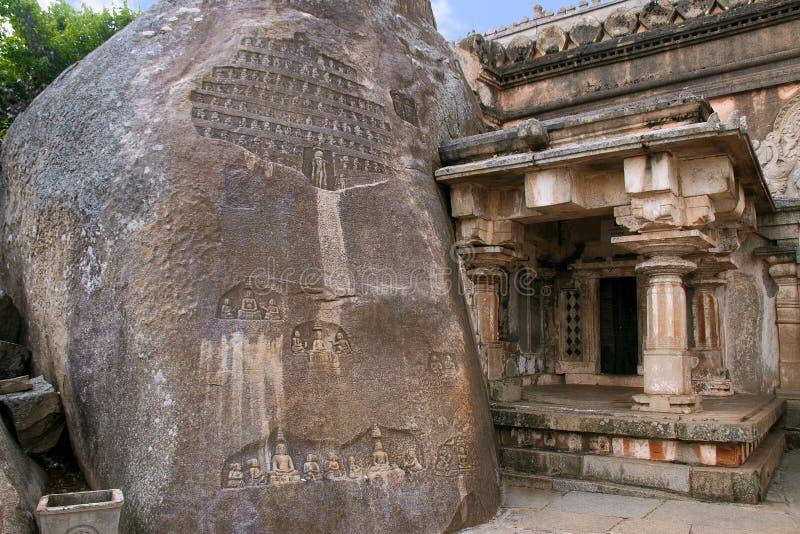 Akhanda Bagilu, Vindhyagiri小山, Shravanbelgola,卡纳塔克邦 与耆那教的圣徒几雕刻的一个巨大的岩石有他们的追随者的 免版税库存照片