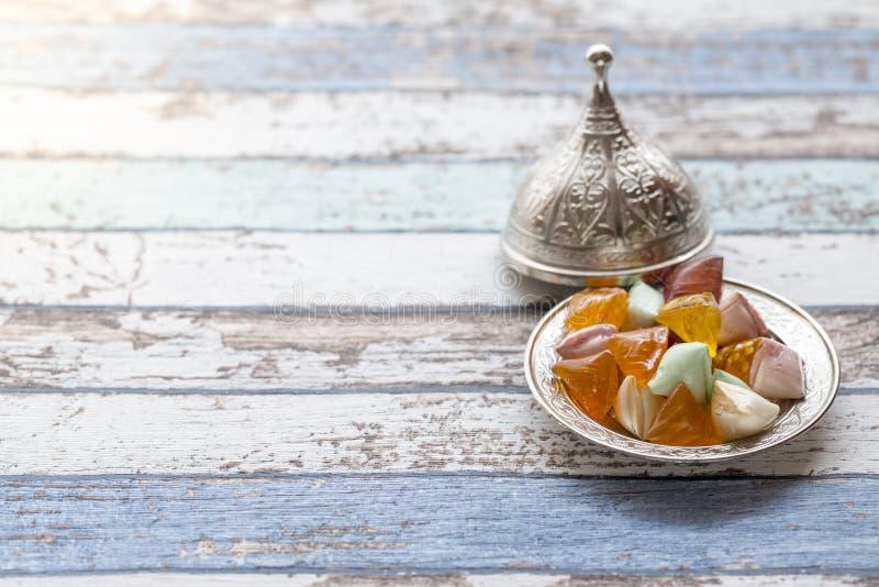 Akide cukrowi cukierki na starym kruszcowym talerzu na rocznika stole obrazy royalty free