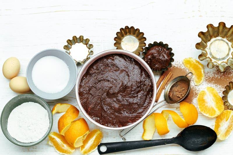 Aking ingredienser av chokladkakan med apelsinskal, kanel och kökredskapet på den vita trätabellen arkivbild