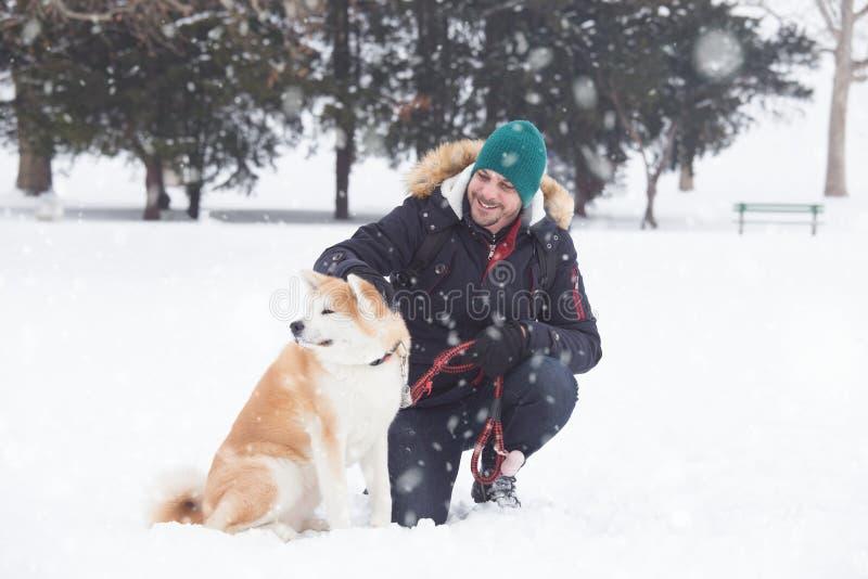 Akita pies z swój właścicielem w śnieżnym dniu zdjęcia stock