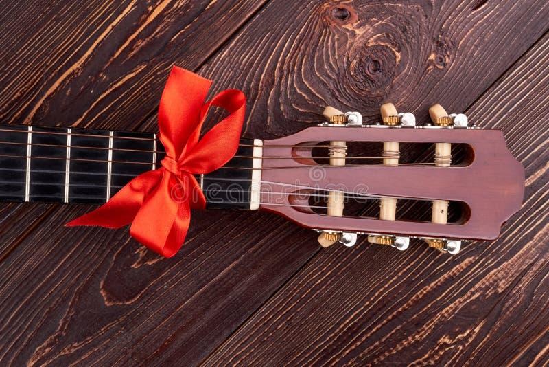 Akoestische gitaar met rode boog royalty-vrije stock afbeelding