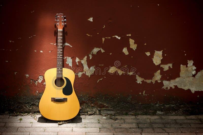 Akoestische gitaar tegen grungy muur royalty-vrije stock foto's
