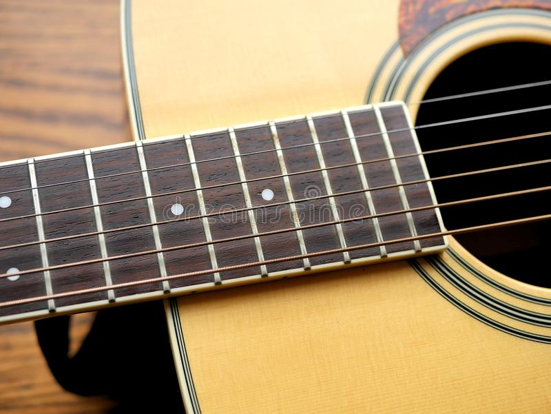 Akoestische houten gitaar dichte omhooggaand op houten achtergrond met fretboard, koorden, en tuners voor muziekbloggen, websiteb stock afbeelding