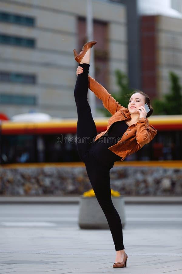 Akrobat som använder telefonen royaltyfria bilder