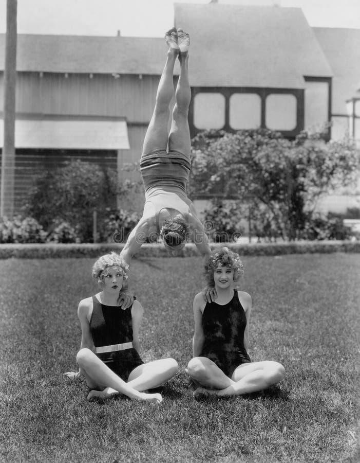 Akrobat som balanserar på kvinnors skuldror (alla visade personer inte är längre uppehälle, och inget gods finns Leverantörgarant fotografering för bildbyråer