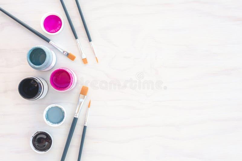 Akrylmålarfärg och målarpenslar på vit bakgrund royaltyfri bild
