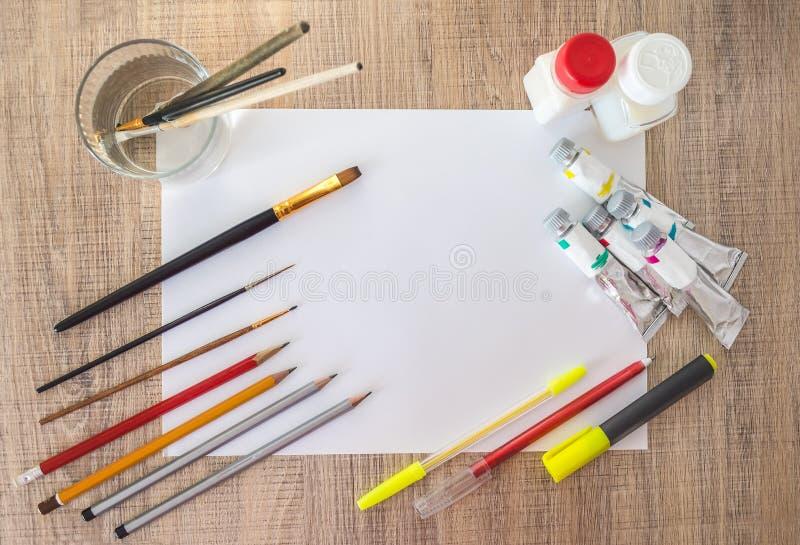 Akrylmålarfärger, målarpenslar, blyertspennor på vitbok Töm utrymme i mitten arkivfoto