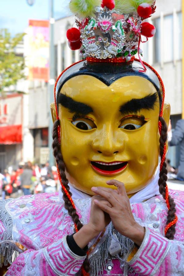 Aktör i maskering och dräkt på den guld- Dragon Parade som firar det kinesiska nya året royaltyfri bild