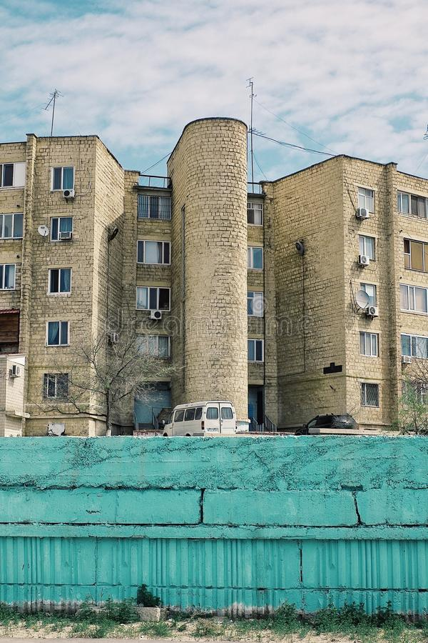 Aktau/Kasakhstan - APRIL 28 2011: typisk kvarterbyggnad som lämnades över från den kommunistiska eran i den moderna staden för nu arkivbilder