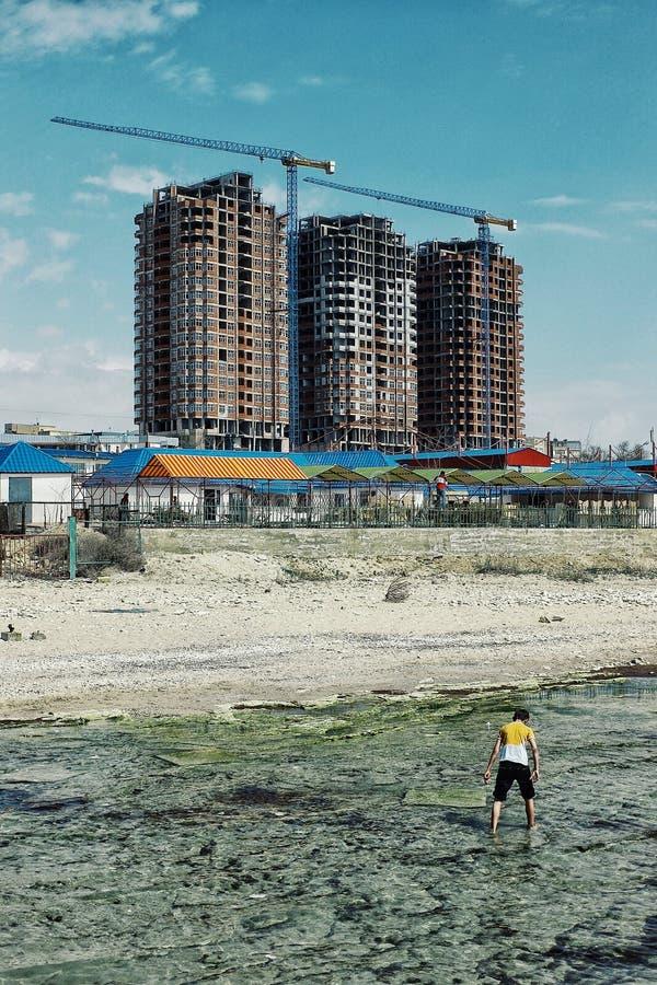 Aktau/Kasakhstan - APRIL 28 2011: typisk kvarterbyggnad som lämnades över från den kommunistiska eran i den moderna staden för nu arkivfoto