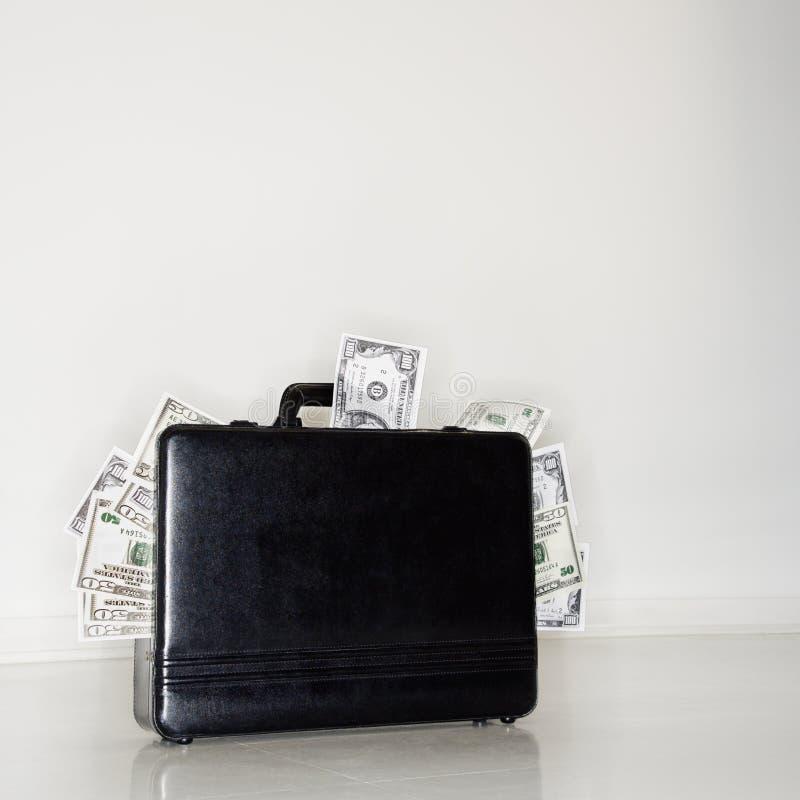 Aktenkoffer, der mit Geld überläuft stockfotos