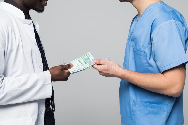 Aktie för medicinsk doktor som muter pengar med kirurgen som isoleras på grå bakgrund fotografering för bildbyråer