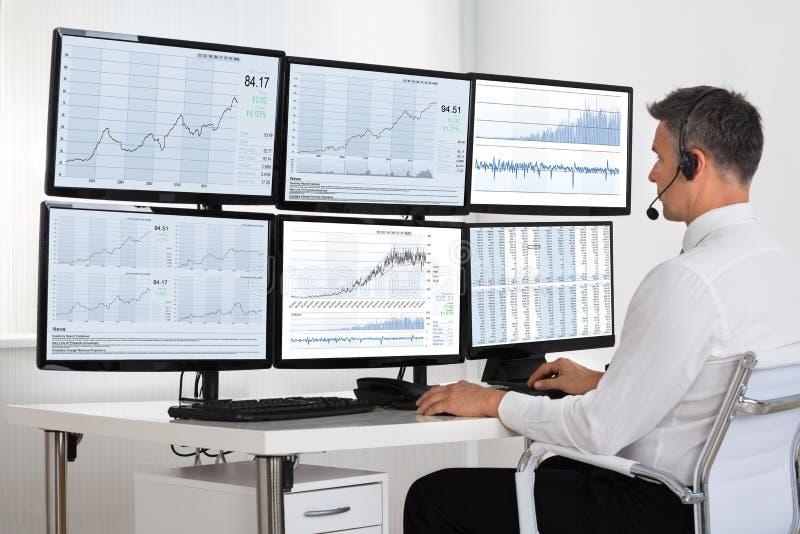 Aktiemarknadmäklare Looking At Graphs på åtskilliga skärmar royaltyfria foton