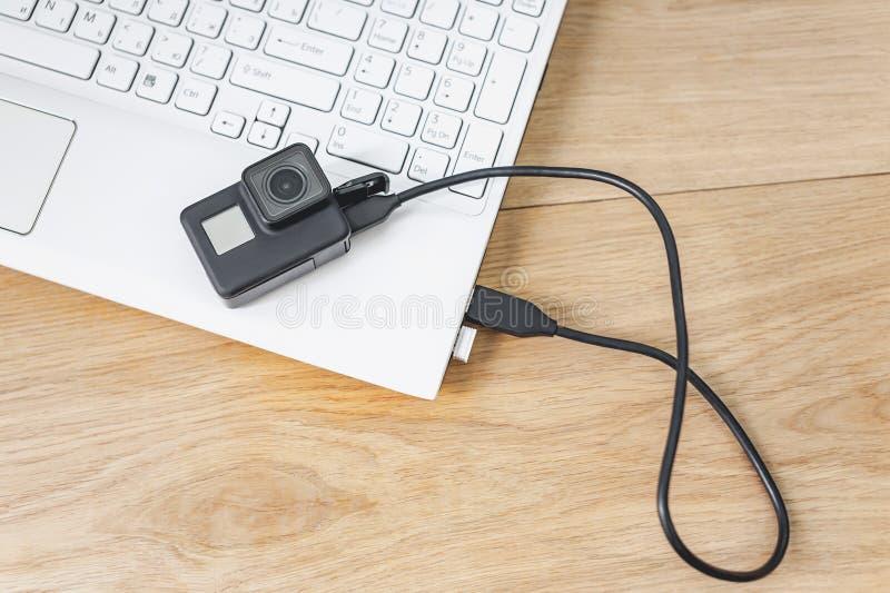 Aktionskamera angeschlossen an einen weißen Laptop, vor dem hintergrund eines Holztischs stockfoto