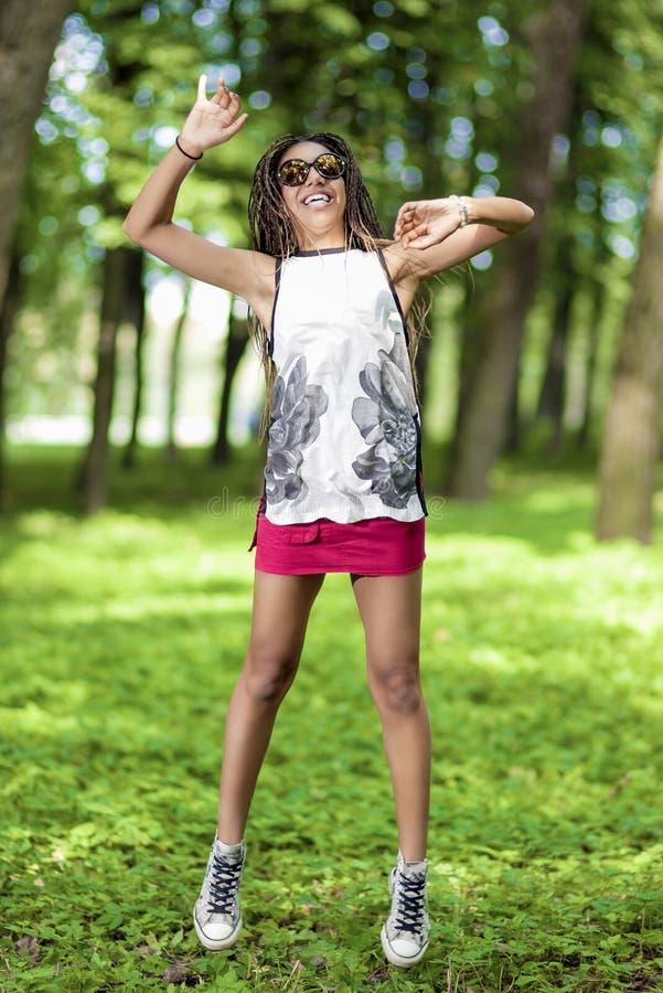 Aktiv afrikansk amerikantonåring med Dreadlocks som gör en höjdhopp med utsträckta händer arkivfoton