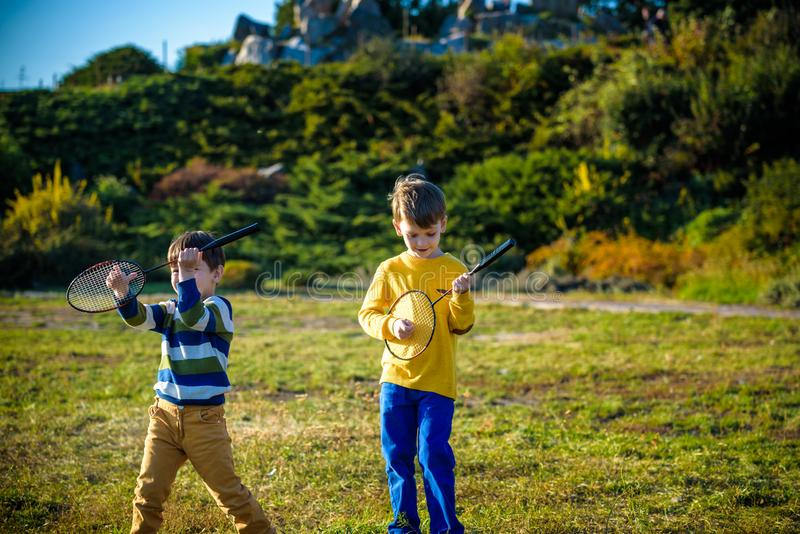 Aktiv förskole- flicka och pojke som spelar badminton i utomhus- domstol i sommar Ungelektennis Skolasportar för barn Racket royaltyfri foto