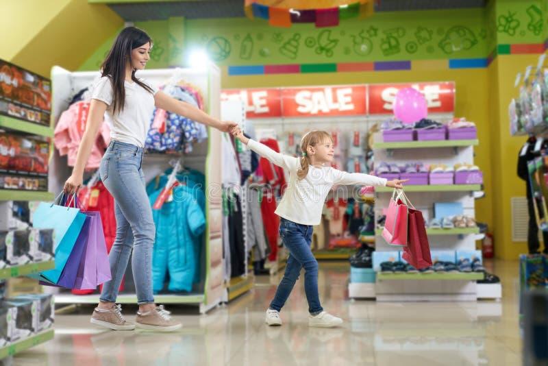 Aktiv familj som håller pappers- påsar och spring i lager arkivfoton